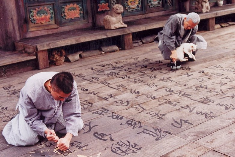 Carving Hieroglyphs on wooden floor - scene from Spring, Summer, Autumn, Winter and then Spring again is a great example of sadness relief through repetitive task