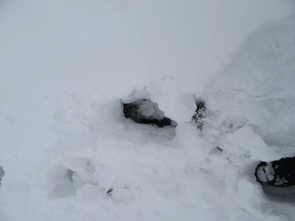 Deep hole made of footstep between the rocks beneath snow