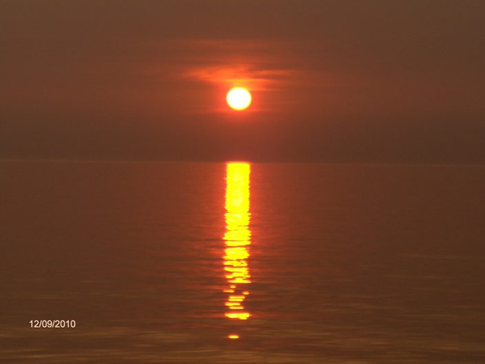 Burning sun setting in the Baltic Sea. Long reflection on the water of orange - red sun. Sventoji, Lithuania, 2010.