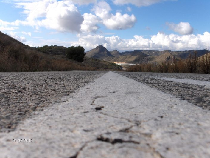 Camera on the road, in the middle. Lane in front goes into the mountain range in the far background, Andalusia, Spain, 2012