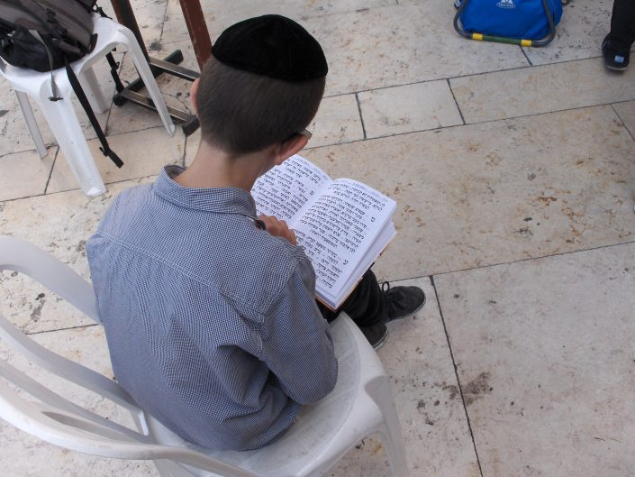 Young jewish boy reading Tora at Wall of Wailings, Israel