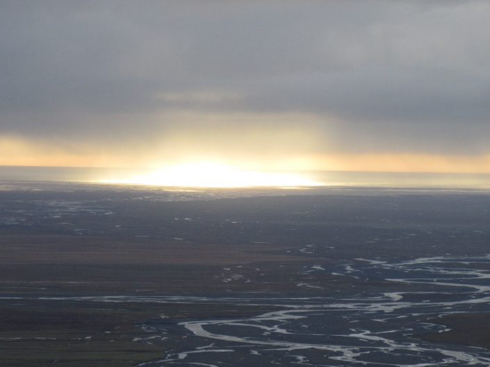 A hike a bit from the ground in Iceland led to wonderful view to the south where sun was playing on the ocean.