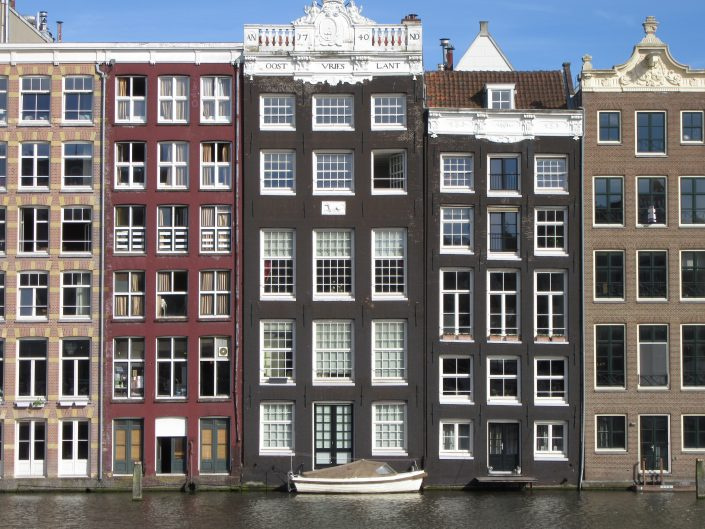 Your typical Amsterdam photo of stacked houses architecture and a boat parked at the front door.