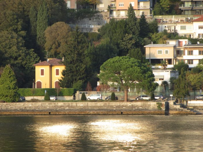 Shore of Italian city Como, near the lago di como (Como Lake) and beautiful sun reflections on the water