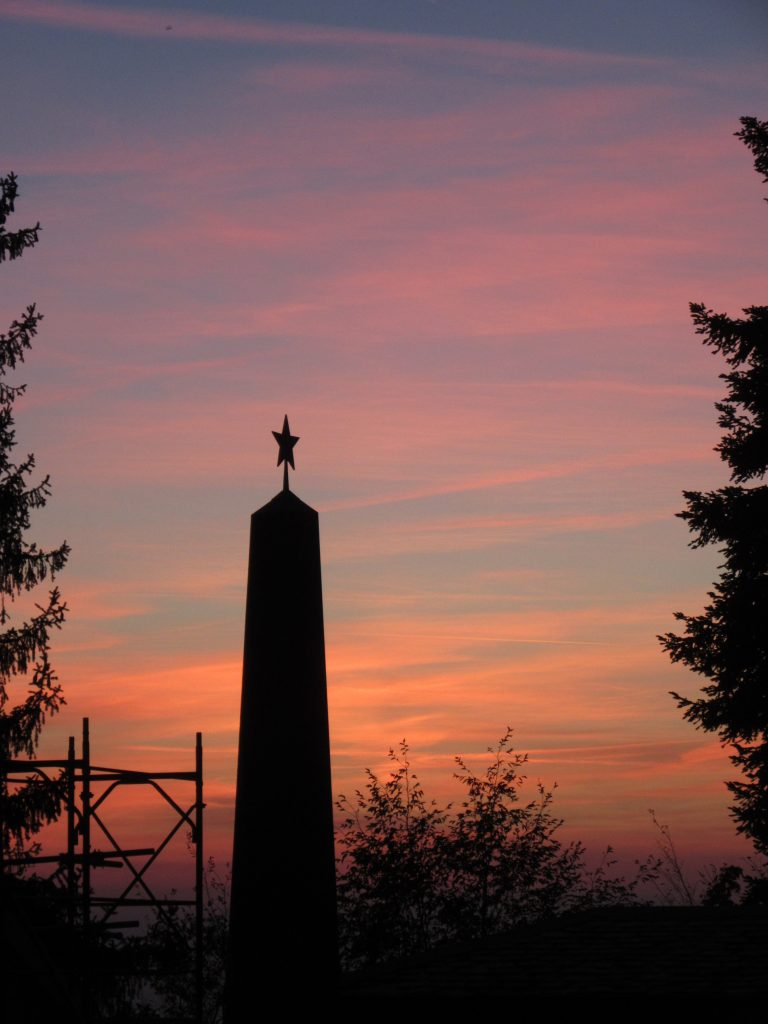 Some monument in Como, Italy with pentagram symbol on top with late evening sky background of reddish orange.