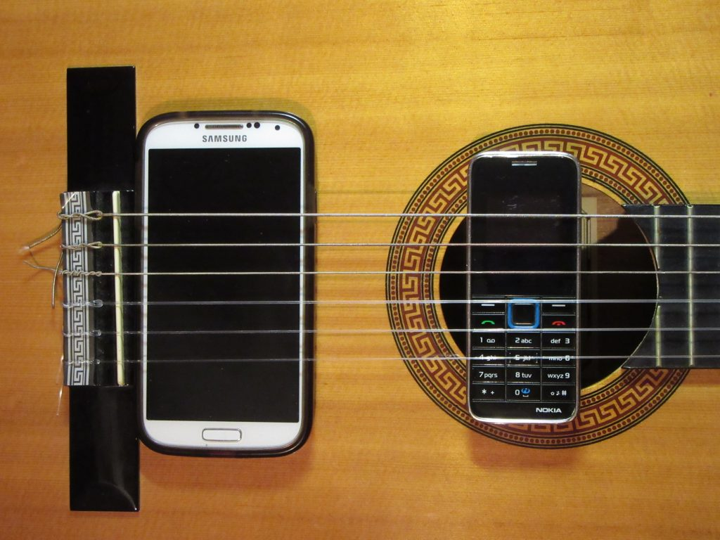 Nokia 3500c And Samsung Galaxy S4 behind Clasical Guitar Strings - image used in Month without internet article