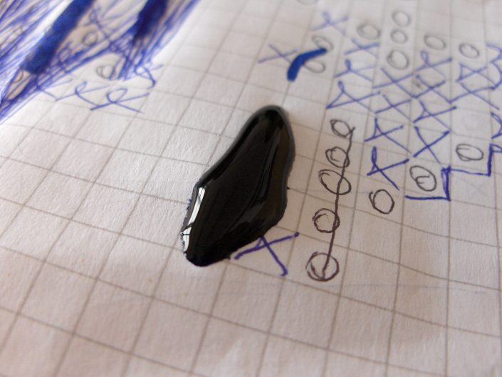 Macro-photography of drop of ink on the school notebook paper