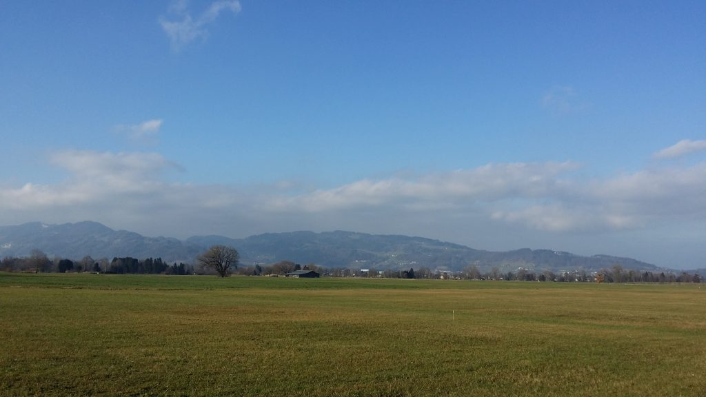 Austria with mountains in far and a wide grass-plot