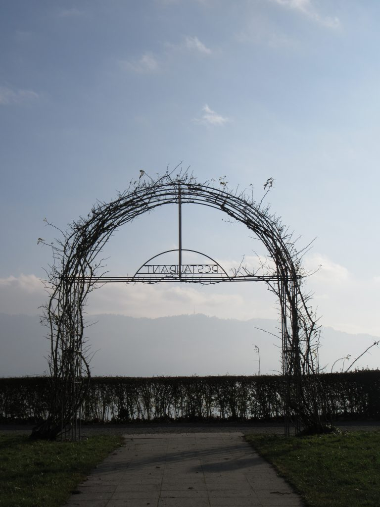 Arc of flowers to bloom in few months leading to a view of mountains in fog and lake of Bodensee, at Lindau, Germany