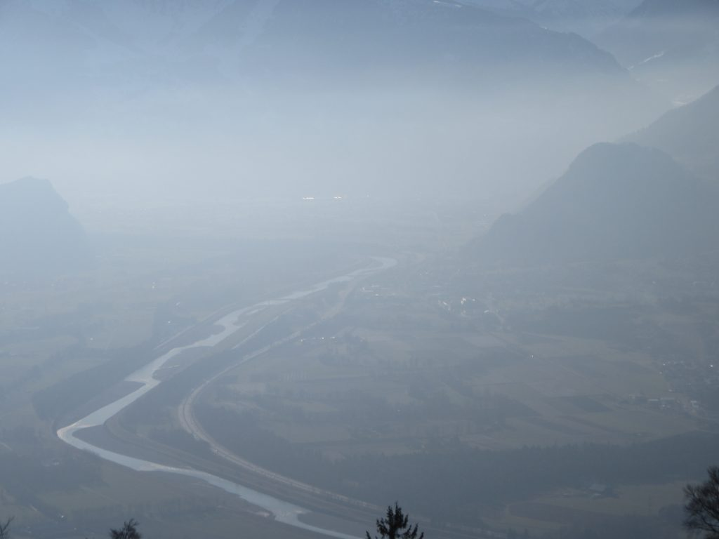 A photo of Liechtenstein from the top. A river and road between mountains and fog.