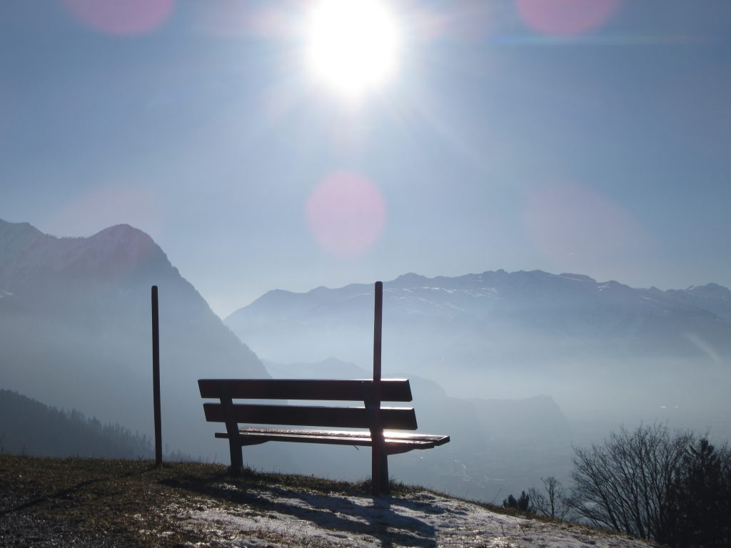 Perfect view bench at Liechtenstein's Alps with an amazing view of mountains in sunny fog.