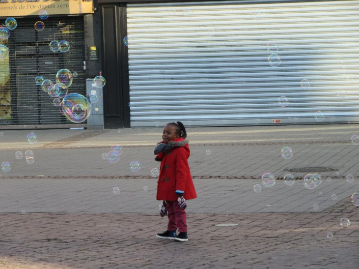 Young black girl observing and smiling at large soup bubbles in the streets of Strasbourg, France