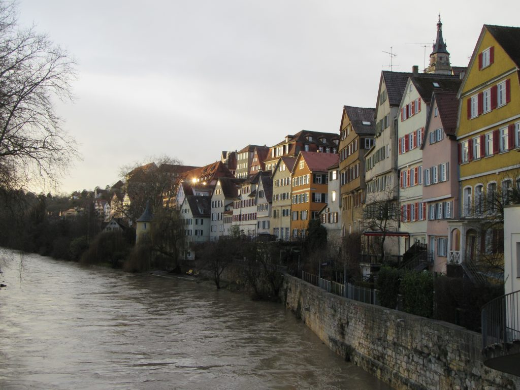 Evening reflections in windows of houses near central river flowing through Tubingen