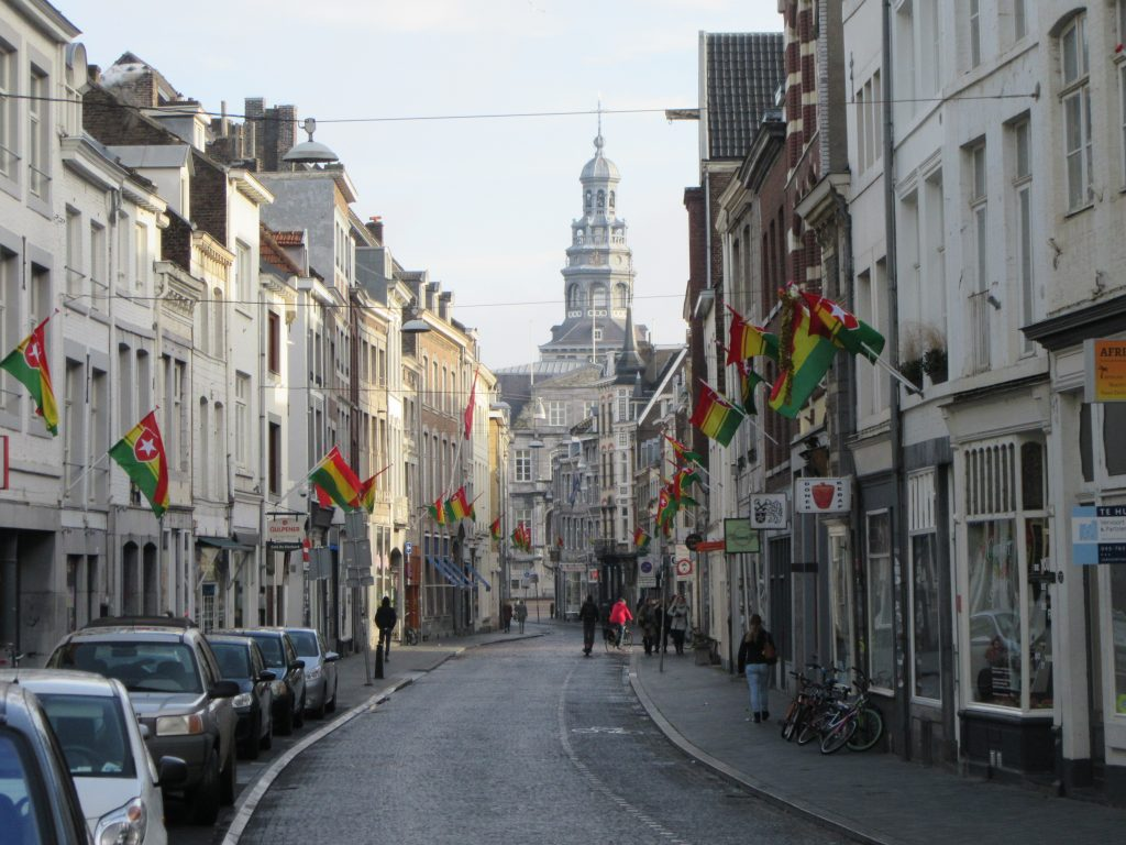 Long street at Maastricht with flags and church at the end of a street