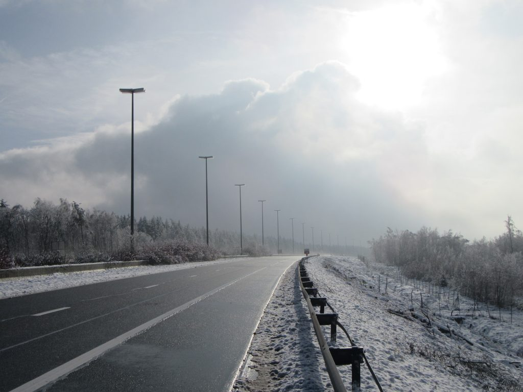Highway, sunny clouds, bit of fog and snow on both sides of the road