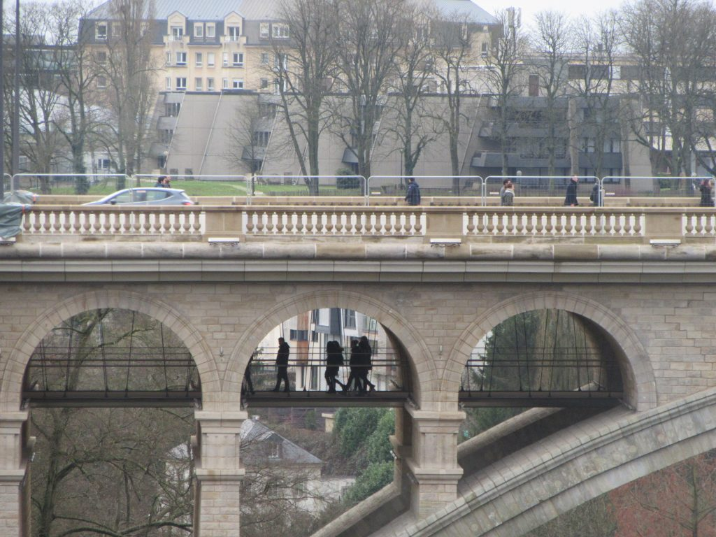 Far shot of people walking under the bridge in Luxembourg