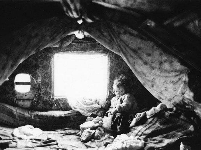 B&W photo of poor girl with sad face in some sort of hut. Photo by Alen MacWeeney