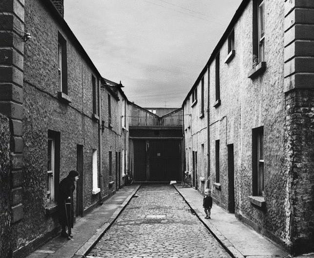 Alen MacWeeney photo of black and white street scene where an old woman and little child are on the opposite sides of the street