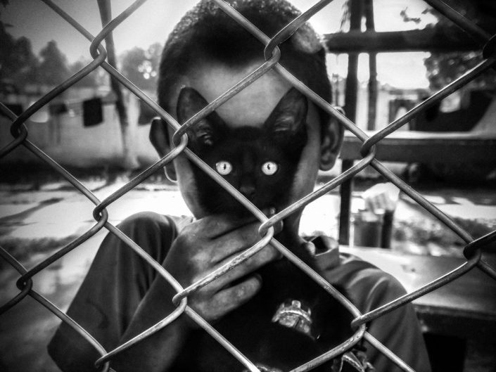 Photo by Arek Rataj of a boy behind a wire fence holding a cat in a place of his face. Black and white.