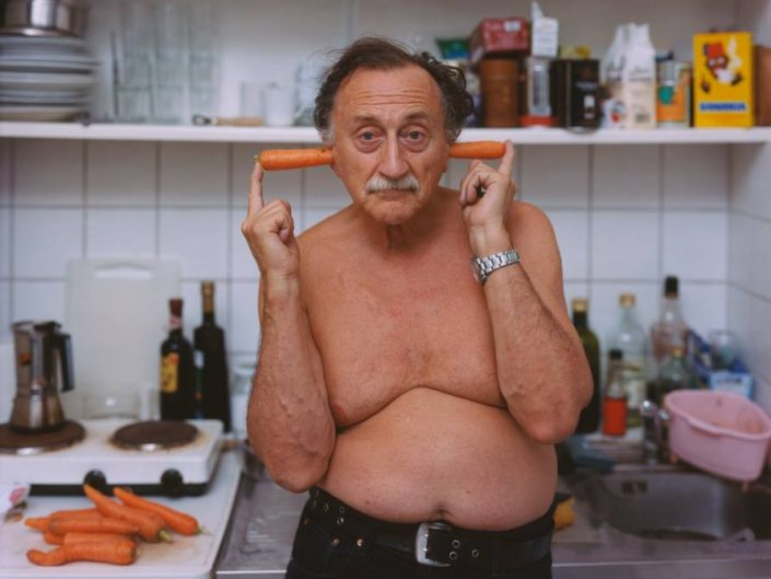 Boris Mikhailov by Alec Soth. Man in the kitchen poses with two carrots pushed into his ears.