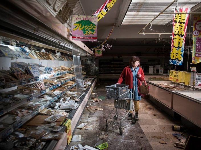 Trashed store and a lone lady with cart inside. Photo by Carlos Ayesta - Fokushima