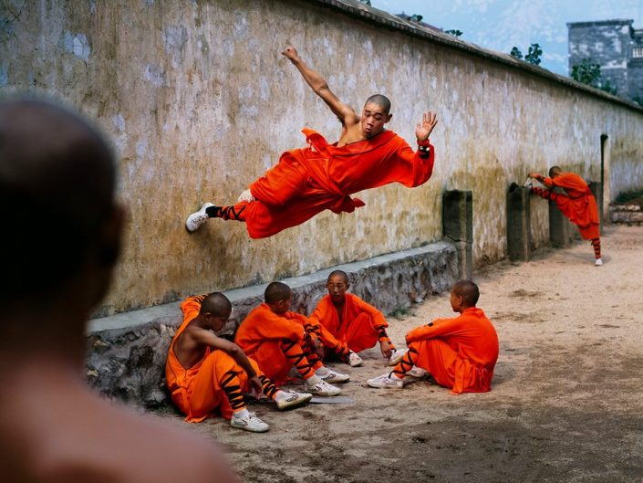 Steve McCurry stop motion photo of monk pushing off from a wall in Shaolin Monastery, 2004