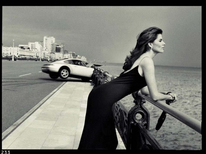Shot by Bob Carlos Clarke of a Car crash caused by beautiful lady leaning at the handrail of the sidewalk looking at the sea.