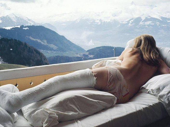 Ed van der Elsken photography of a girl with broken leg lying enjoying at least the view of gorgeous mountains.