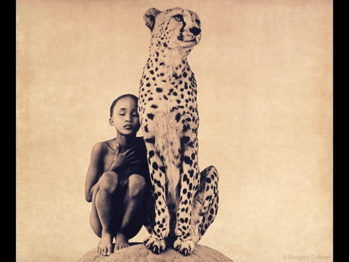 Scene from Ashes and Snow by Gregory Colbert - boy with closed eyes sitting with a cheetah besides him.