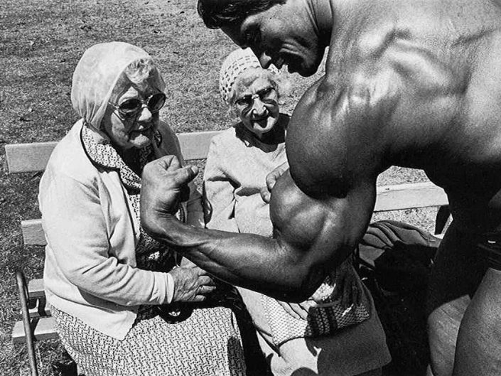 Professional Photography by Helen Levitt of Arnold Schwarzenegger posing his biceps in front of two old ladies in the park of New York, 1988