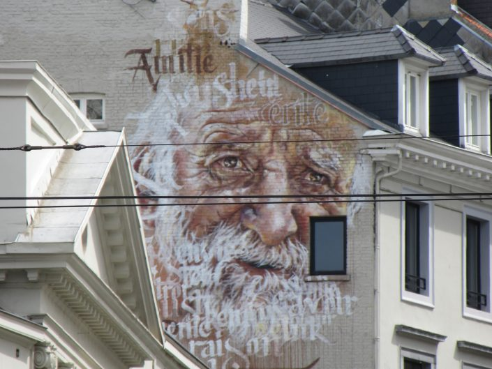 Street art painting of old man with text embedded in his beard and forehead seen in Brussels, Belgium 2017