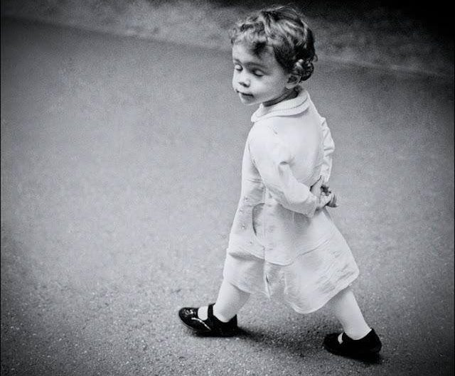 Ioana Moldovan B&W photograph of little girl walking on a street posing extravagantly with her mimics.