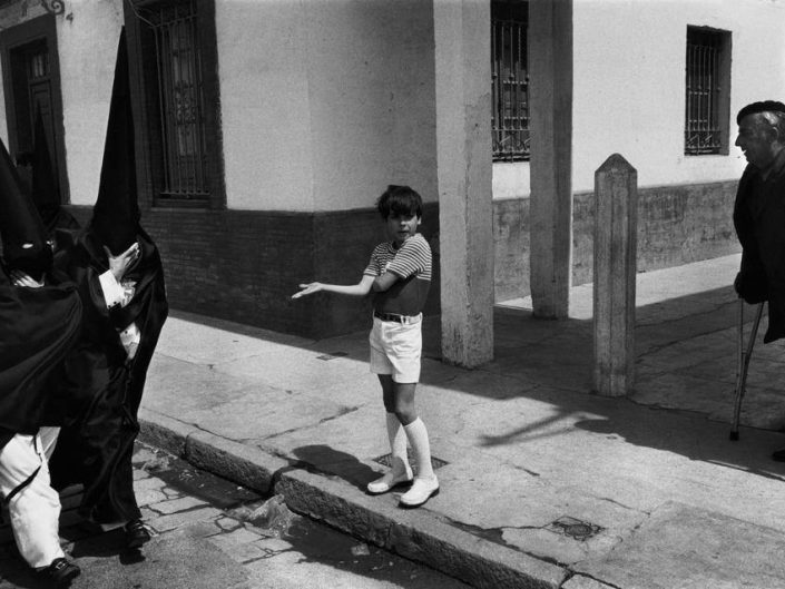 "Josef Koudelka caught a moment in black and white of KKK clan members passing by while a boy on the sidewalk is wondering ""what the hell"""