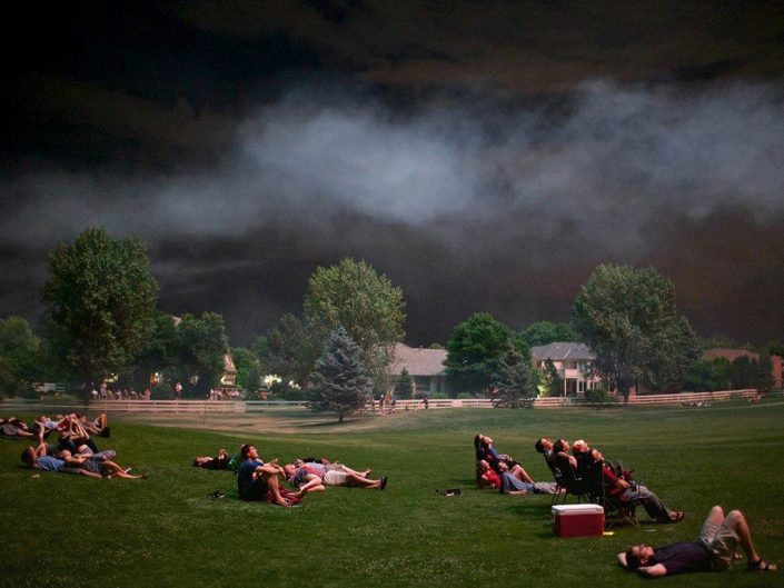 Matthew Borowick - Independece Day. People on the ground looking at the sky while sky in the background is extremely dark and storm promising