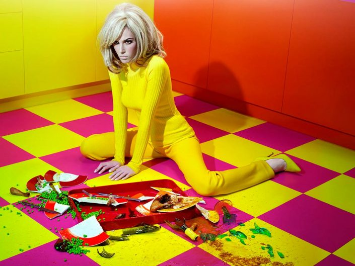 Miles Aldridge cinematic photo of vivid colors and angry looking girl besides broken plates on the ground