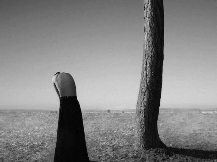 Noel S. Oszvald black and white photo of a woman's back and a sole tree in a vast field. Tree is curved. Lady's head is facing down.