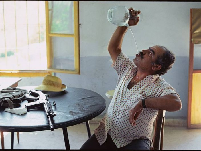 Raymond Depardon photo of a man drinking a water in a weird way, with an automated gun besides on a table