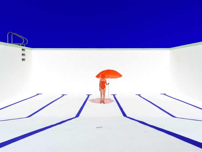 Person in an empty pool standing with umbrella.