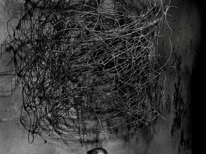 Scared person below twirling wires. Photography by Roger Ballen