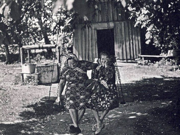 Romualdas Rakauskas photography in black and white depicting two old women on swings, laughing.