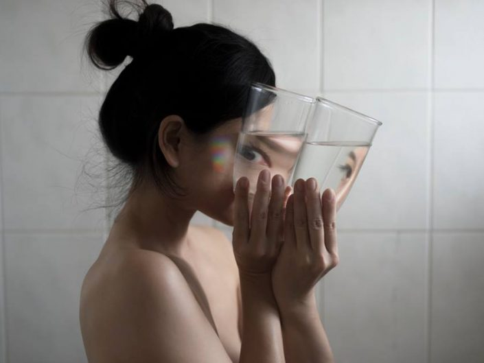 Profile portrait photography by Yung Cheng Lin of an asian girl holding a glass, so that eye is unnatural.