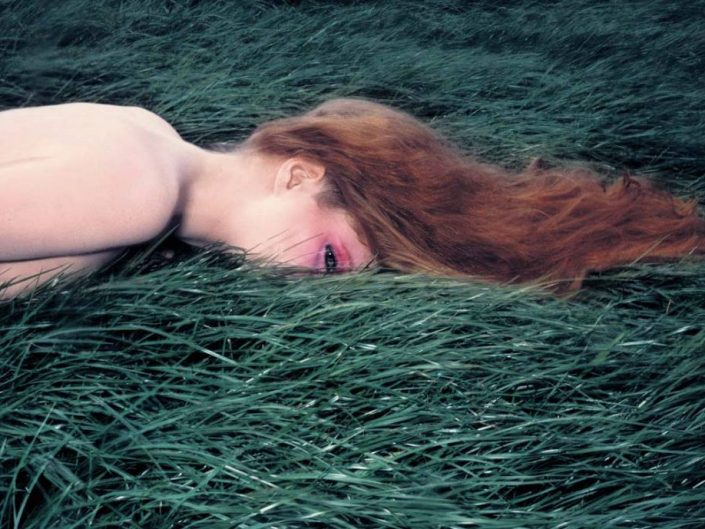 Guy Bourdin photo of a wind playing inside the field and hair of woman hiding among the tall grass. One flow.