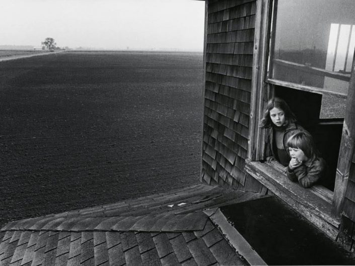 Larry Towell black and white photography of two kids looking through the window at the flat huge, dark field