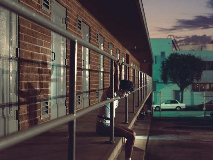 Philip Lorca diCorcia. Man resting his head on pipe of a balcony rail. Deep enticing city lights.