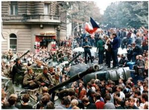 Peaceful obstruction and resistance to the Warsaw Pact invasion of 1968. Many people in the streets. Some with flags on the tanks. Milan Kundera book review image