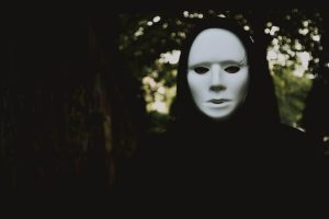 A man in dark clothing wearing a white mask - symbolic of ego mask we all carry around