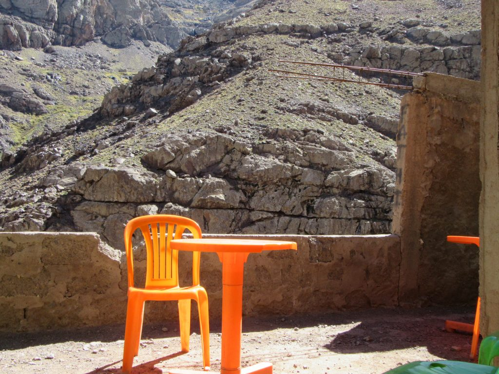 Orange, plastic chair and table in the background of Atlas mountains, Morocco, Jbel Toubkal Route, Generalistlab
