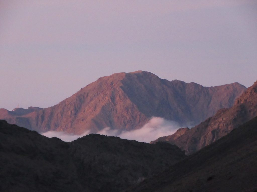 Sun setting and coloring the mountain in the far in dark red color with white clouds below