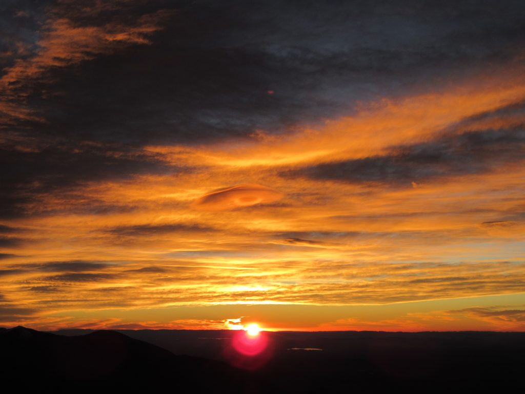 Red clouds and sunrise in the horizon at Jbel Toubkal Summit Peak October 2018