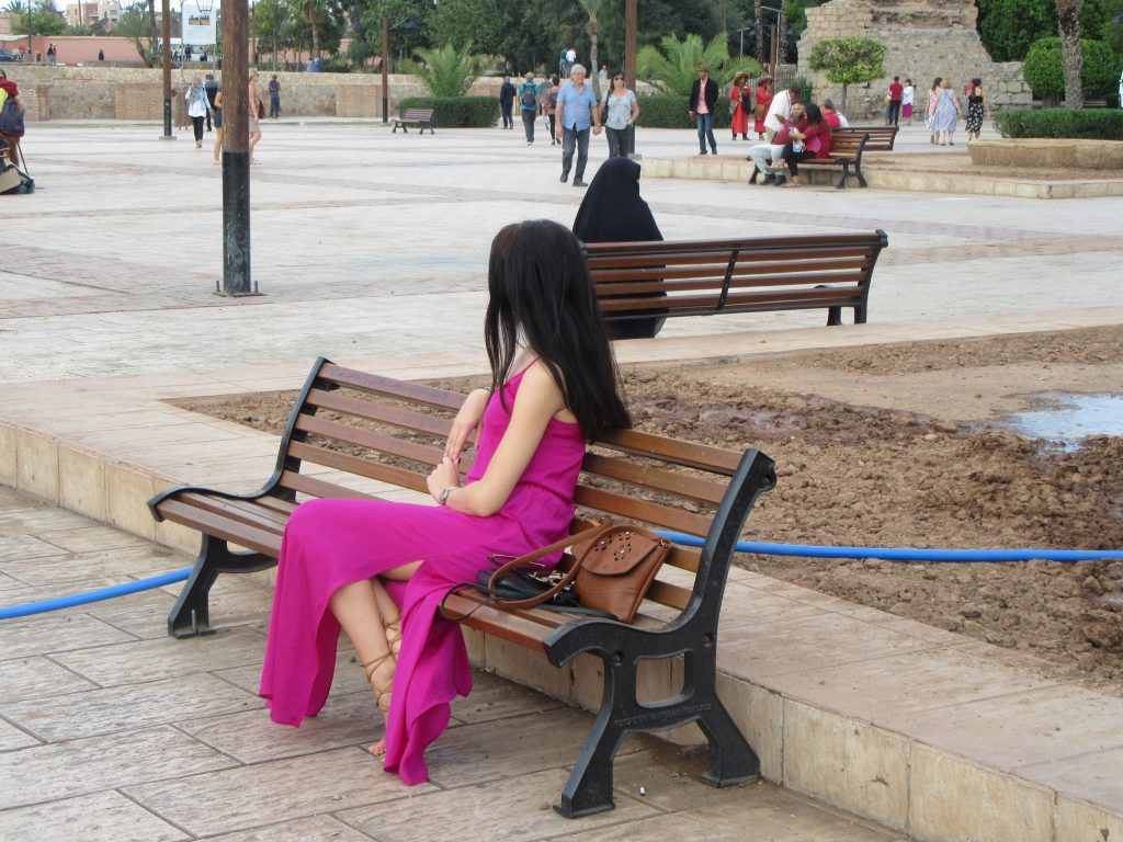 Woman in dress posing while another in the background is in burka